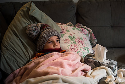 Canada, Ontario, Boy in knit hat lying on sofa covered with blanket - p924m2283070 by Viara Mileva