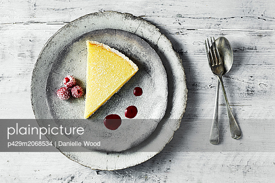 Still life with lemon tart and raspberries on plate, overhead view - p429m2068534 by Danielle Wood