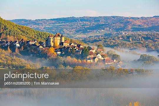 Curemonte labelled l'un des plus beaux villages de France (most beautiful villages in France) in the morning mist in the autumn, Correze, Nouvelle-Aquitaine, France - p651m2085200 by Tim Mannakee