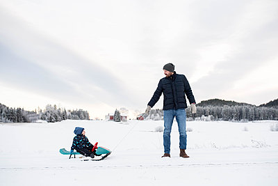 Father son walking sledging in snow white forest winter wonderland - p1166m2096357 by Cavan Images