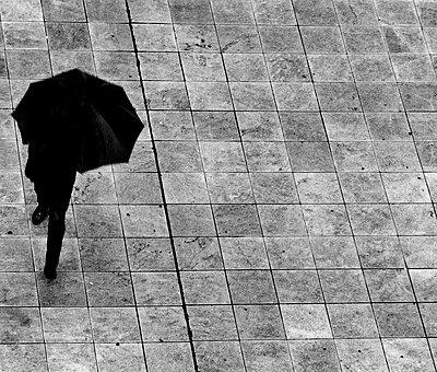 Man with black umbrella - p1445m2150457 by Eugenia Kyriakopoulou