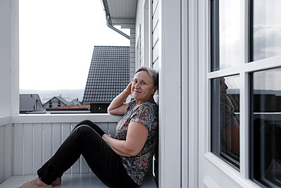 Portrait of smiling relaxed senior woman sitting on porch - p300m2103370 by Katharina Mikhrin