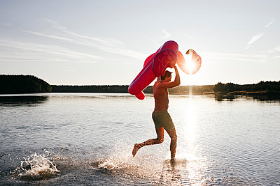 Young man running with flamingo pool float into a lake - p300m2143904 by Ekaterina Yakunina