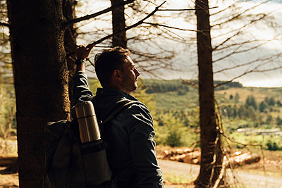 Thoughtful male hiker with backpack standing by tree trunk in forest - p300m2213915 by Boy photography
