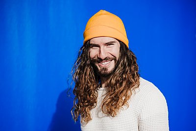 Smiling male hipster in front of blue cloth during sunny day - p300m2274041 by Eva Blanco