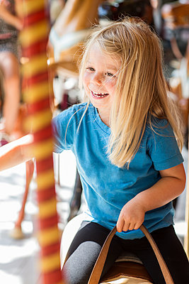 Small girl riding carousel - p312m1229134 by Peter Rutherhagen