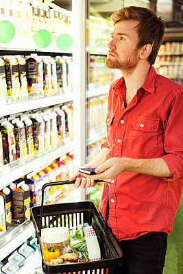Man holding mobile phone while shopping at refrigerated section in supermarket - p426m1017984f by Maskot