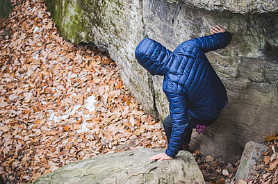 Man in Jacket and Hood Climbing Down Rocky Hiking Path - p694m1221865 by Eric Schwortz