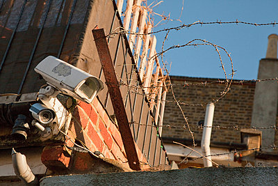 Surveillance camera and barbed wire - p9242799f by Image Source