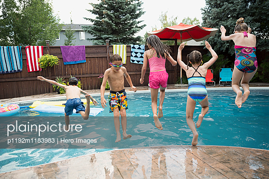 Boys and girls jumping into swimming pool - p1192m1183983 by Hero Images