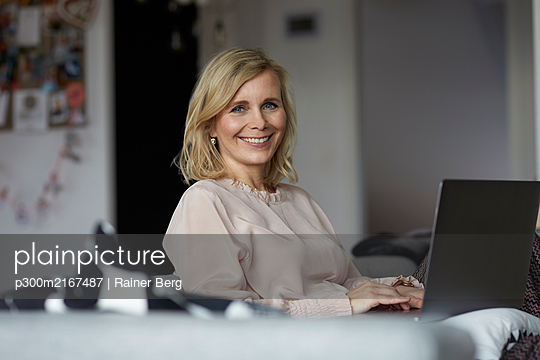 Portrait of smiling blond woman using laptop at home - p300m2167487 by Rainer Berg