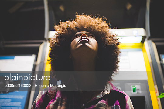Young woman with afro hairdo at ticket machine at night looking up - p300m2180932 by Eugenio Marongiu