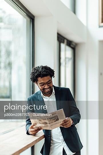 Smiling male professional reading newspaper while leaning desk in office - p300m2287703 by Gustafsson