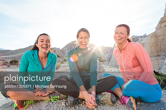 Laughing women sitting in canyon - p555m1305371 by Michael DeYoung