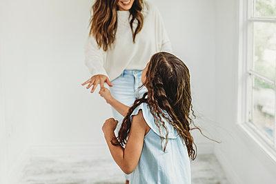Daughter and mother dancing in natural light studio - p1166m2130755 by Cavan Images