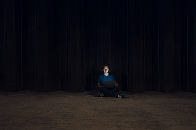 Mid adult man sitting cross-legged on ground, using laptop at night - p300m2029321 von Gustafsson