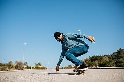 Trendy man in denim and cap skateboarding - p300m2029431 by Josep Rovirosa
