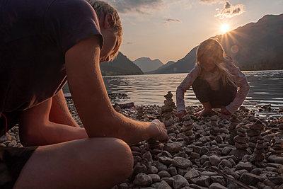 Austria, Ausseer Land, Children building cairns at lakeshore - p300m2060023 by Hans Mitterer