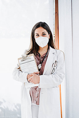 Female medical expertise with protective face mask holding clipboard while standing against glass window - p300m2265047 by Eva Blanco
