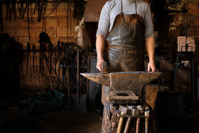 Male blacksmith standing with hammer by anvil at shop - p300m2281450 by Antonio Ovejero Diaz