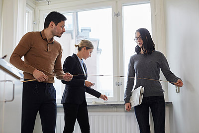 Couple taking measurements while standing with realtor in new house - p426m2097635 by Maskot