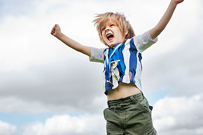 Boy with medals cheering outdoors - p429m746865f by Colin Hawkins