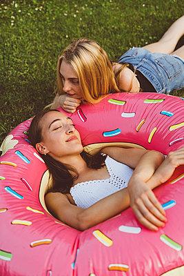 Freundinnen entspannen mit Donut Schwimmreifen im Garten - p432m2260275 von mia takahara