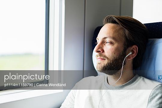 junger Mann hört im Zug Musik - p1114m1159790 von Carina Wendland