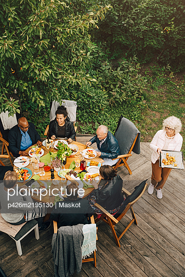 High angle view of woman serving meal to senior friends sitting at dining table during garden party at back yard - p426m2195130 by Maskot