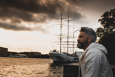 Man at harbor in Stockholm, Sweden - p352m2040978 by Henrik Andersson