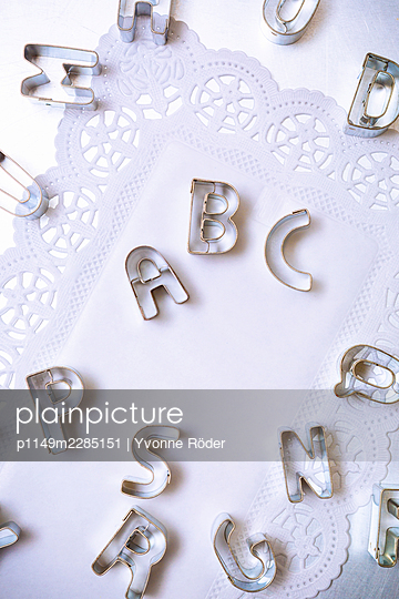 Alphabet cookie cutters on paper doilies - p1149m2285151 by Yvonne Röder