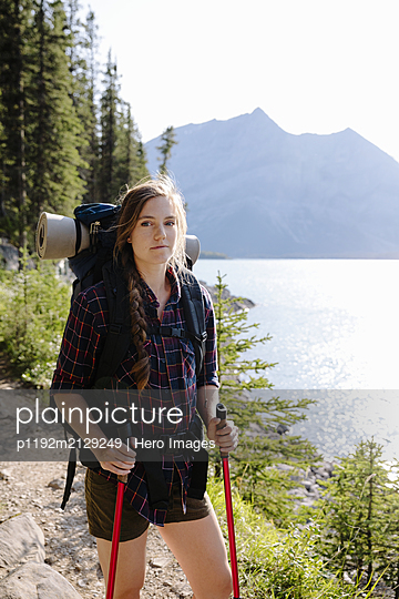 Portrait confident backpacker hiking on trail along sunny lakeside - p1192m2129249 by Hero Images