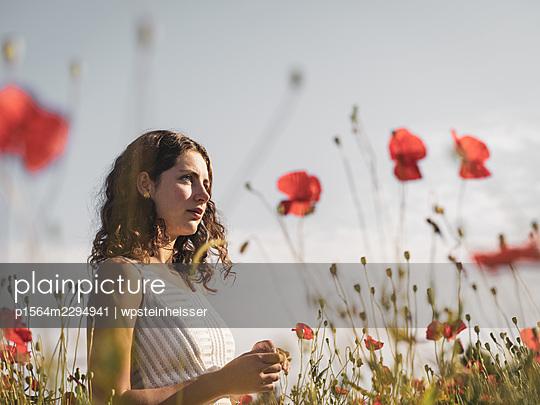 Teenage girl in summer in a flowering meadow - p1564m2294941 by wpsteinheisser