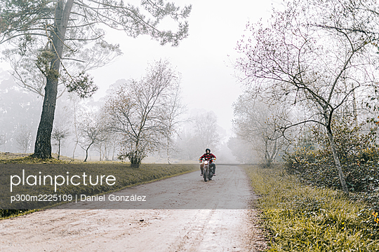 Man riding motorcycle on dirt road in foggy weather - p300m2225109 by Daniel González