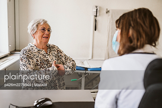Senior female patient discussing with healthcare worker while consulting during COVID-19 - p426m2279844 by Maskot