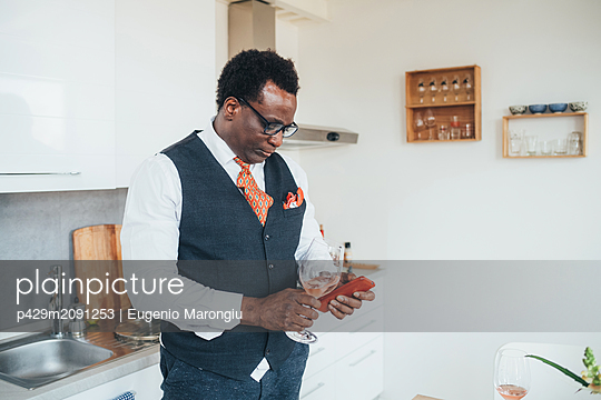 Businessman using smartphone in kitchen - p429m2091253 by Eugenio Marongiu