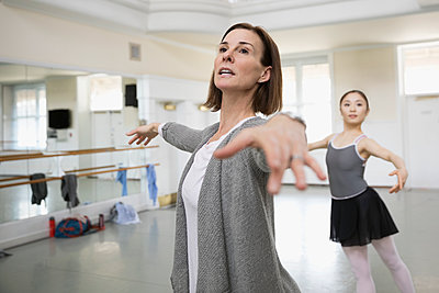 Female instructor guiding ballet dancer practicing in dance studio - p1192m1403476 by Hero Images
