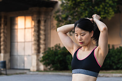 Determined woman tying hair while exercising in park - p300m2243297 by NOVELLIMAGE