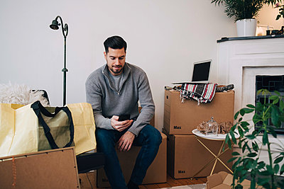 Mid adult man using mobile phone while sitting on box at home - p426m1542783 by Maskot
