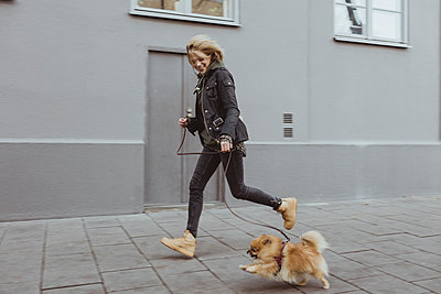 Full length side view of happy woman running with her Pomeranian dog on footpath by building in city - p426m2194768 by Maskot