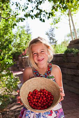 Caucasian girl holding basket of cherries - p555m1480000 by Marc Romanelli