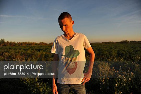 Jugendlicher mit Kurzhaarschnitt auf einem Feld - p1468m1585014 von Philippe Leroux