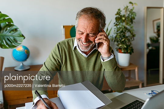 Smiling man writing in book while talking on mobile phone at home - p300m2227235 by Valentina Barreto