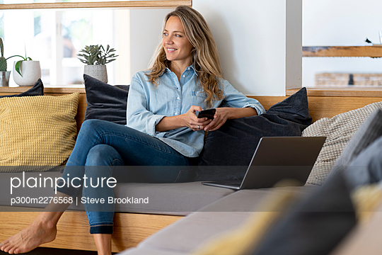 Woman sitting with mobile phone and laptop on couch n living room - p300m2276568 by Steve Brookland