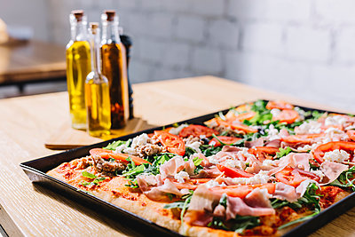 Close-up of pizza in tray on table at pizzeria - p1166m2040268 by Cavan Images