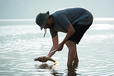 Fisherman holding a fish near riverside - p1315m2055881 by Wavebreak