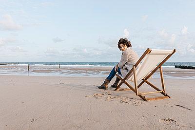 Woman sitting on deckchair on the beach - p300m1499381 by Kniel Synnatzschke