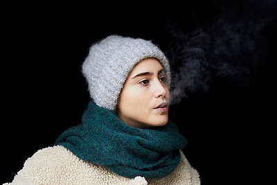 Portrait of  young woman in winter clothes smoking - p300m2083401 by Jo Kirchherr