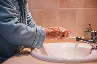 Senior woman washing hands by sink at home - p300m2243796 by DREAMSTOCK1982