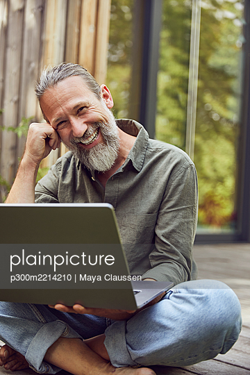 Smiling mature man with laptop sitting outside tiny house - p300m2214210 by Maya Claussen